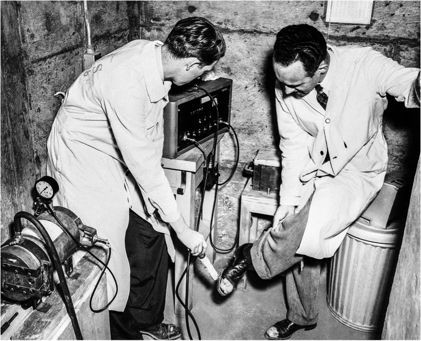 Dr. Ralph Overman uses a probe counter to check the shoes of Dr. Waldo E. Cohn for radioactive contamination on June 14, 1946 in Oak Ridge, Tennessee (AP Photo/Clinton Labs; taken from snippits-and-slappits.blogspot.com via Bing Images).
