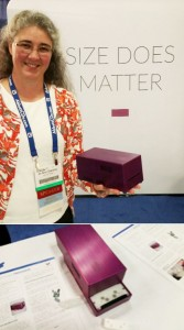 My personal photo of Dr. Jo-Ann Stanton holding a Freedom4 qPCR instrument that slides open to access four sample tubes.
